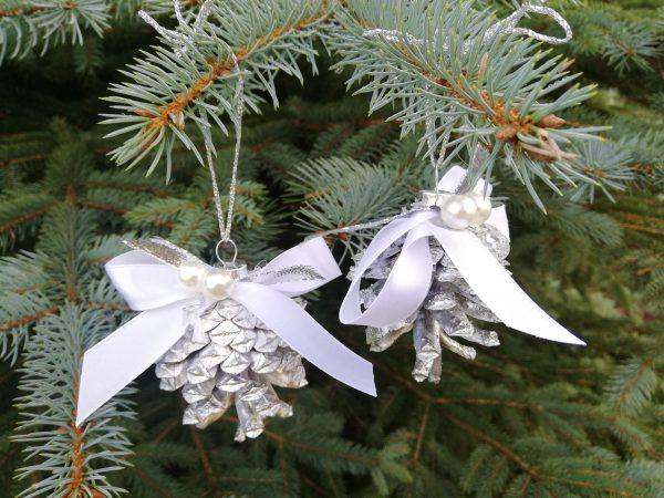 https://artdecha.pl/wp-content/uploads/2019/11/bombki-na-choinkę-srebrne-z-szyszek-z-białą-kokardą-na-Boże-Narodzenie.jpg